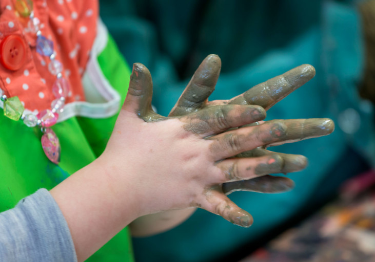 Child hands with mud